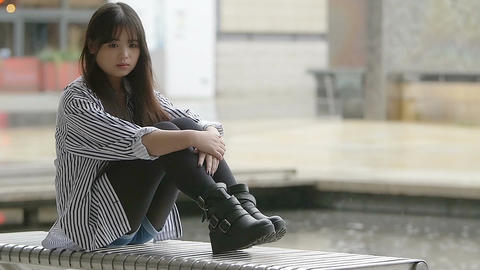 slow motion footage of young asian woman sitting lonely with rain in background Footage