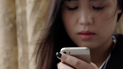 worried and sad asian woman typing a short message on the mobile phone Filmmaterial
