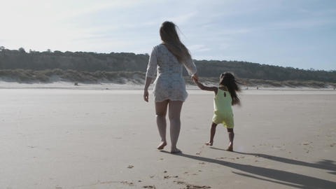 Mom and little daughter holding hands and walking on beach Acción en vivo