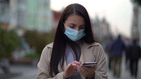 Portrait woman in protective medical mask walks down to the street uses phone Acción en vivo