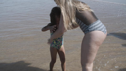 Mom wearing swimsuit, walking on beach to water Acción en vivo