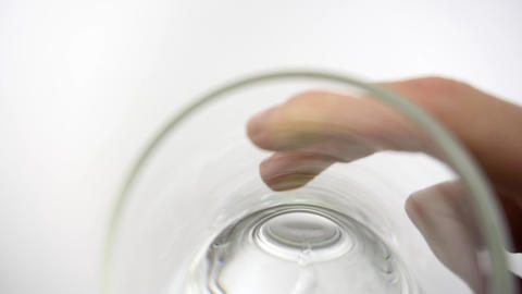 Man's hand is holding clear glass with water and drinks from it 실사 촬영
