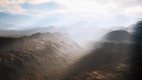 aerial vulcanic desert landscape with rays of light GIF