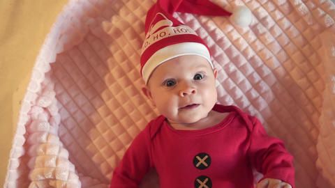 Smiling Santa child lying in santa claus costume, in red hat, red pajamas Live Action
