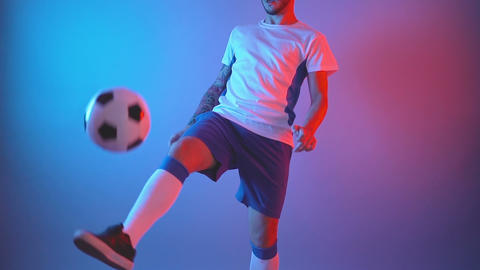 football in professional uniform juggling ball in studio red and blue lights Live Action