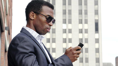 young handsome businessman using cell phone or smartphone in the city Footage