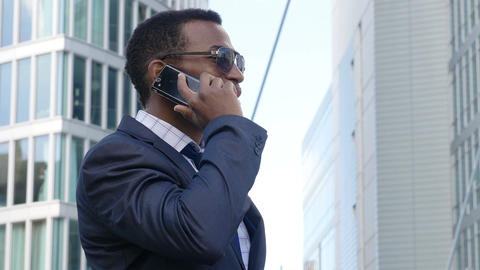 young African American businessman in a business conversation using mobile phone Footage