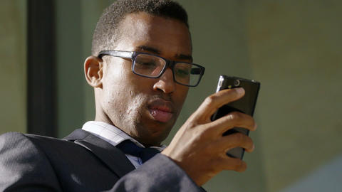 handsome African-american businessman texting messages on his smartphone Footage