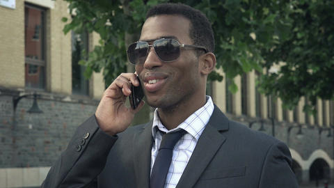 young attractive african american businessman using smartphone in the city Footage