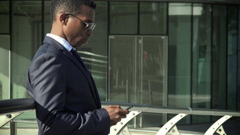 handsome elegant black businessman using cell phone: texting a message or email Footage