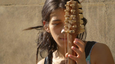 portrait of a young east european woman playing a string in the street Footage