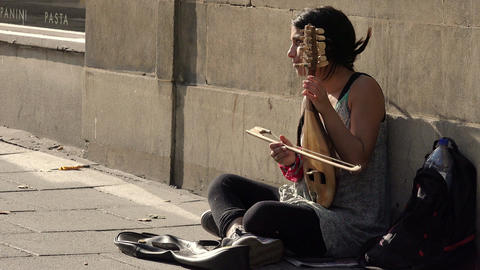 playing music in the street: street artist playing string instrument Footage