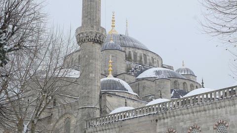 detail of the minaret of the ancient mosque, snow falling and birds flying Footage