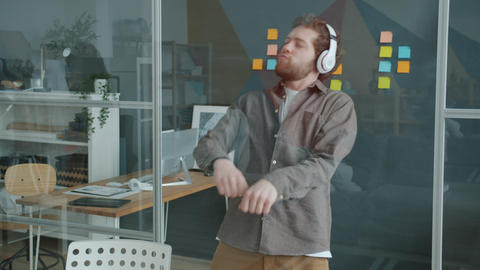 Slow motion of joyful guy dancing in workplace wearing wireless headphones Acción en vivo