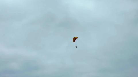 Sky diver descending on parachute overcast sky Live Action