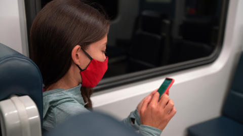 Face mask concept. Woman wearing mandatory mask in public transportation. Train Live Action
