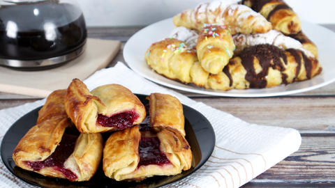 Breakfast served on the table. Sweet delicious pastry with cherries and sweet croissants and coffee Live Action
