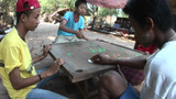 A Group Of Young Adults Play A Game Using Green And White Chips Near Buddhist Temples In Pagan Of Bu stock footage