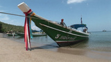A Boat Sits In The Shallow Water Along A Beach stock footage
