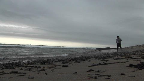 A jogger runs on a beach Stock Video Footage