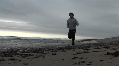 A jogger runs on a beach Stock Video Footage
