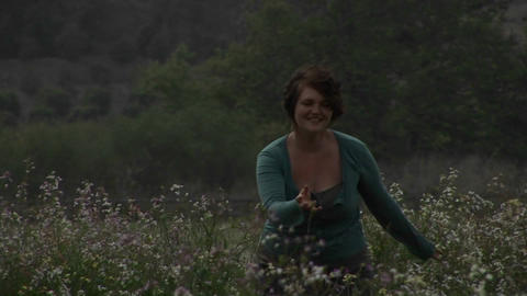 A woman walks through wildflowers Stock Video Footage