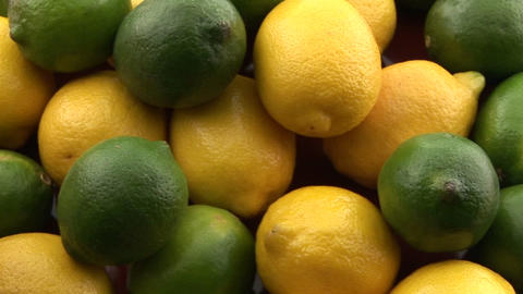 A pile of lemons and limes sits on a table Footage
