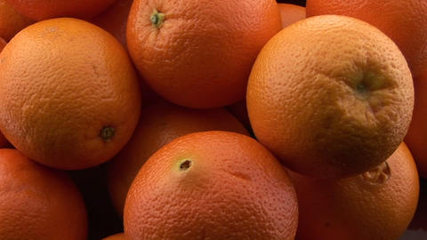 A pile of oranges sits on a table Stock Video Footage