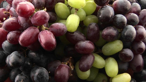 Purple, red, and green grapes sit in a cluster Stock Video Footage