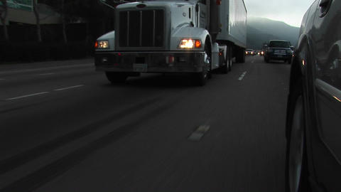 Cars and trucks drive by on a crowded highway Stock Video Footage