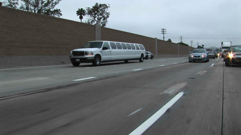 A stretch limo drives down a freeway Stock Video Footage