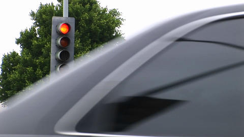 Traffic drives pass a street light Stock Video Footage