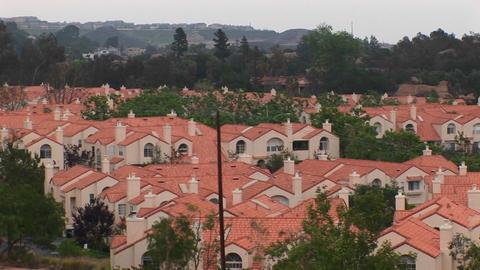 Thick vegetation surrounds a neighborhood of stucco homes Footage