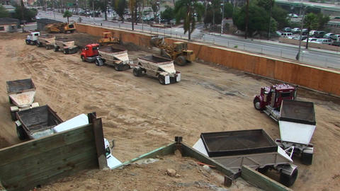 A back hoe dumps a load of dirt into the trailer of a semi Stock Video Footage