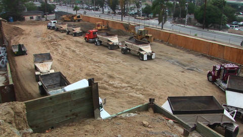A back hoe dumps a load of dirt into the trailer of a semi Live Action