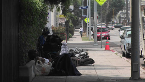 Homeless men sit on a sidewalk Stock Video Footage
