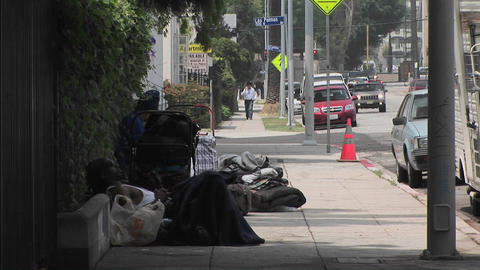Homeless men sit on a sidewalk Footage
