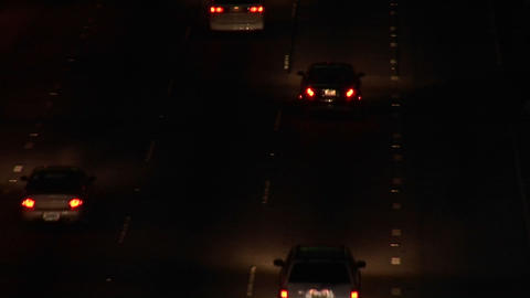 A rack-focus of vehicles driving on the freeway at night Stock Video Footage
