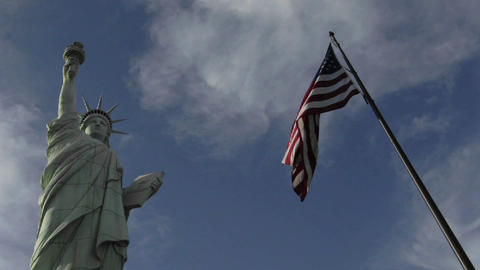 A time lapse of clouds moving over the Statue of Liberty and an American flag Footage