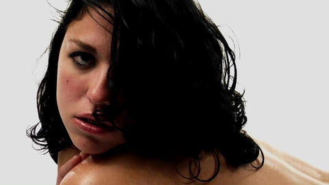 A topless woman with damp hair looks in the direction of the camera Footage