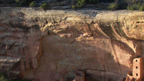 A cliff rises above Pueblo Indian dwellings in the Mesa Verde National Park, Colorado Footage