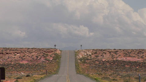 A deserted desert road and clouds in the sky Footage
