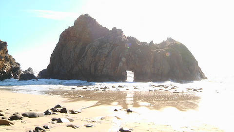 Waves roll into shore on a sunny day along California coastline with an arch rock foreground Footage