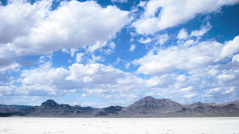 Time lapse of clouds moving over salt flats or desert Stock Video Footage