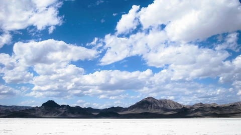 Time lapse of clouds moving over salt flats or desert Footage