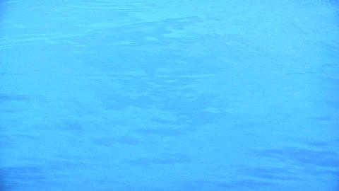 Water drops hitting an expanse of very blue water Stock Video Footage