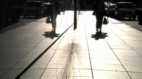 Pedestrians are silhouetted as they pass along a sidewalk... Stock Video Footage