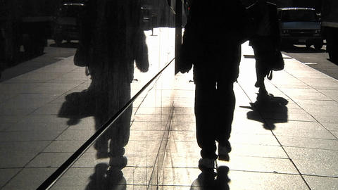 Pedestrians are silhouetted as they pass along a sidewalk in a city Footage
