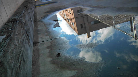 Time lapse of clouds passing over an urban building as reflected in a puddle on the pavement Footage
