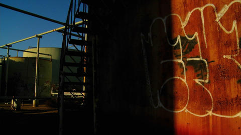 Time lapse of a graffiti covered wall passing into shadow in an industrial area Footage